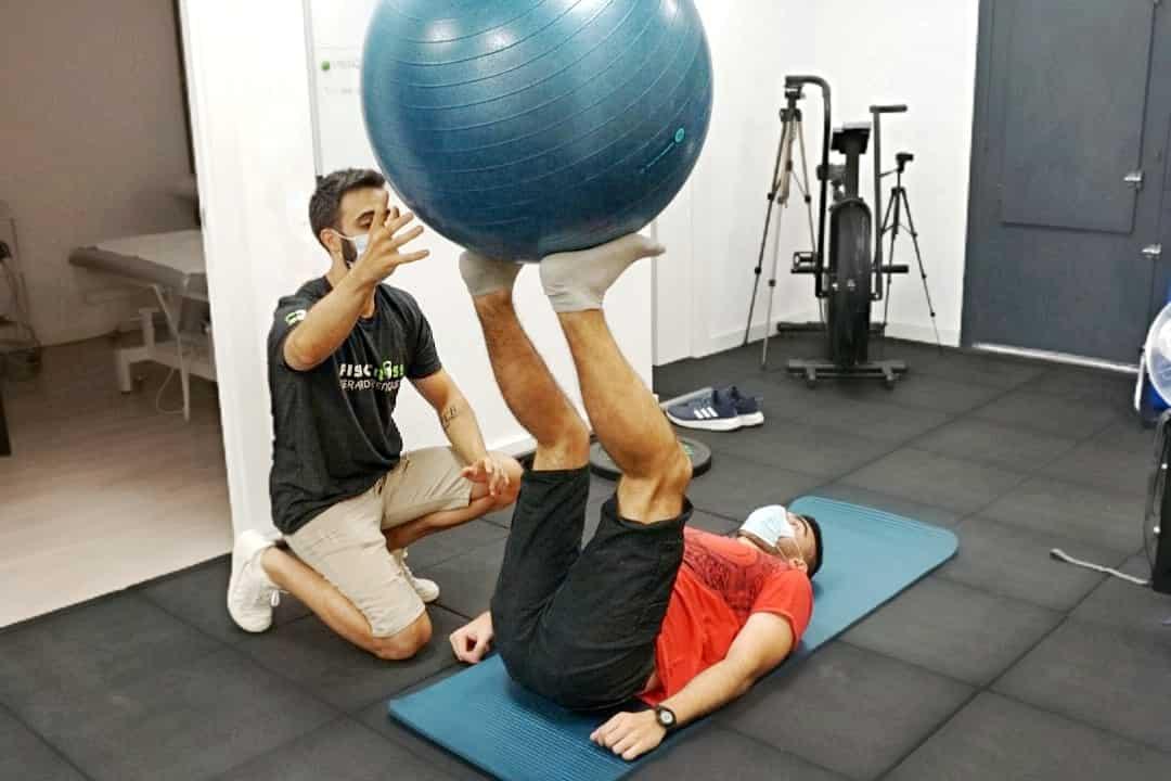 Fisioterapeuta con paciente en rehabilitación de extremidad inferior